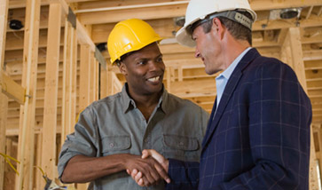 Two men in hard hats shaking hands on construction site